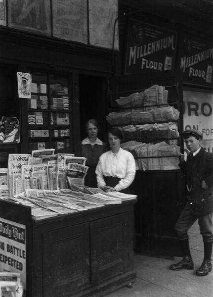News stand on the platform of Truro station during the First World War. Two ladies and a young boy stand for the photograph. The picture shows many copies of newspapers and magazines for sale. There is also an advertisement for Millennium Flour