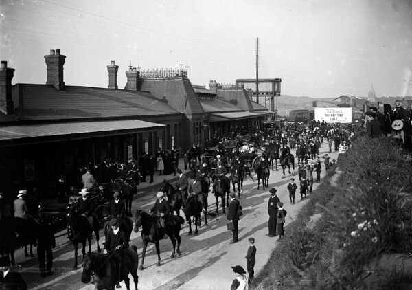 A crowd of people including many horse riders outside the station