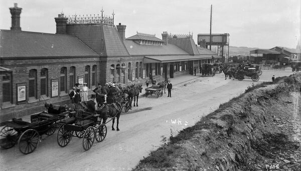 Exterior view of Truro Railway Station with horse drawn carriages waiting outside, including two carriages from the Red Lion Hotel