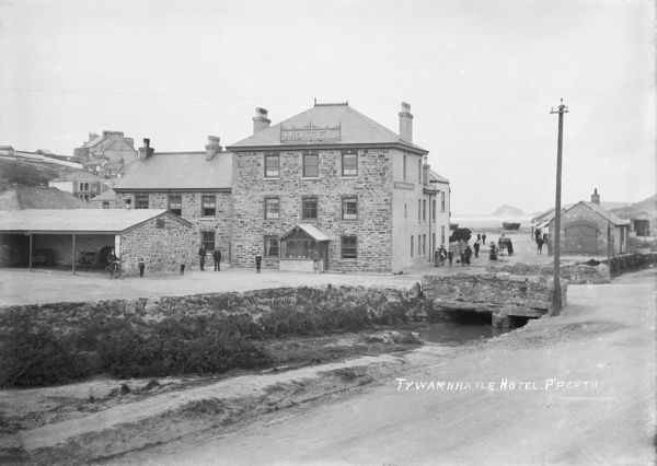 Tywarnhayle Hotel with the Rocket Brigade building (Rocket life-saving apparatus). A view down Beach Road to the sea with boats on the bar in the background and several horse drawn vehicles. Photographer: Arthur Philp