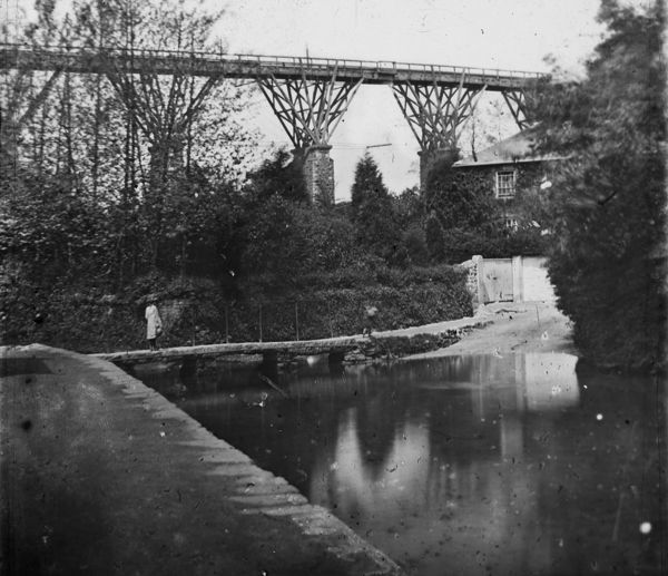 Image shows a woman crossing the Moresk footbridge which was replaced with a road bridge in 1881 with Brunel's Moresk viaduct in the background
