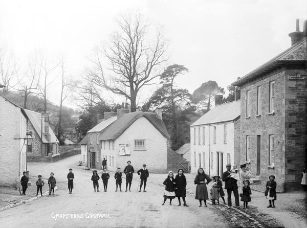 Bottom of the village, looking west to the cottage near the school. Several people, including a large number of children, are posed in the road. Photographer: Samuel John Govier
