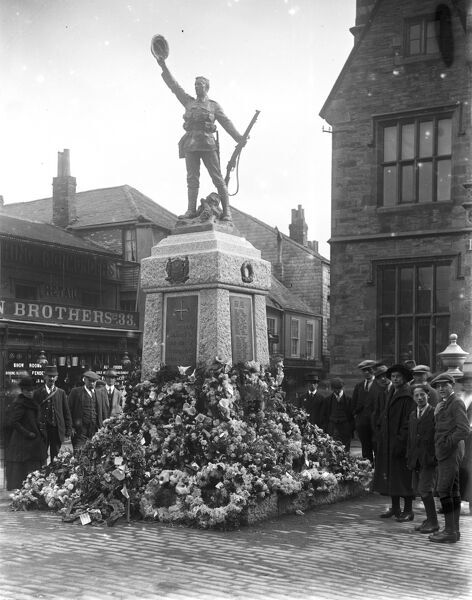 Wreath-bedecked memorial, with onlookers. Memorial unveiled on 15 October 1922. Photographer: A W Jordan