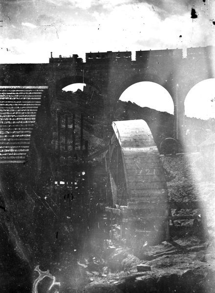 Stamps and waterwheel in the foreground and the viaduct for the Helston branch line in the background, with a steam train and carriages travelling across it