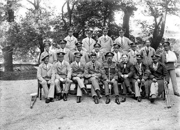 Wounded soldiers posed in uniform with trees in the background. Photographer: Arthur William Jordan