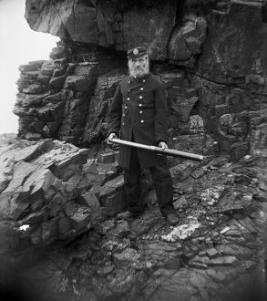 Coastguard with telescope below cliff, Padstow, Cornwall. Early 1900s