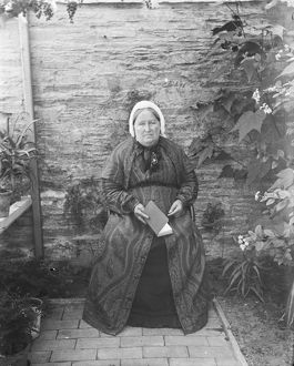 Elderly lady seated by a wall. Padstow, Cornwall. Possibly 1890s