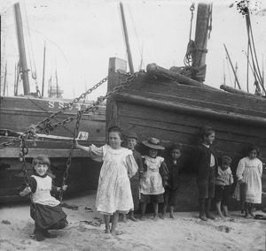 A group of children with fishing vessels at St Ives harbour, Cornwall. Early 1900s