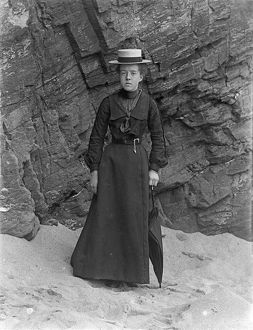 Lady standing below cliff at Padstow, Cornwall. Probably 1890s or early 1900s