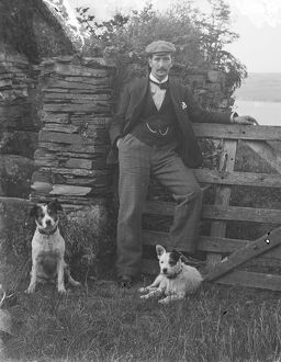 Man with two dogs posed by gateway at St Saviour's Point, Padstow, Cornwall