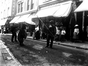 Performing bear, Market Street, Falmouth, Cornwall. Early 1900s.