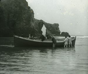 "Thought to be Perranporth Arch Rock, with children playing on the boat ""The Ocean Waif"". Cornwall"