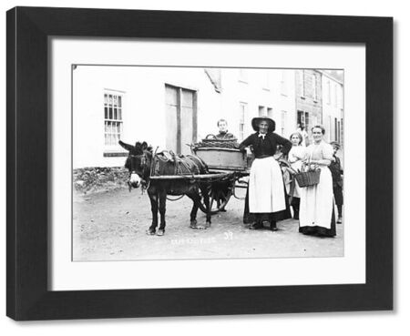 Vegetable sellers posing in the street with their donkey and cart, curious children enjoying the scene in the background. Photographer: Samuel John Govier