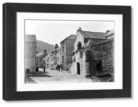 View along a street on a sunny day in Polperro. Note the three young children playing and the fisherman's oilskin trousers hanging on a door to dry at the right of the picture. Photographer: Herbert Hughes?