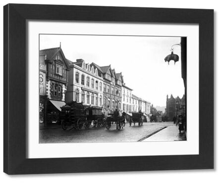 Horse drawn vehicles, including the horse bus 'Princess', in Boscawen Street, outside the Red Lion Hotel. Looking east along the street. A sign, in the shape of a sheep, hangs from the building opposite. Photographer: Unknown