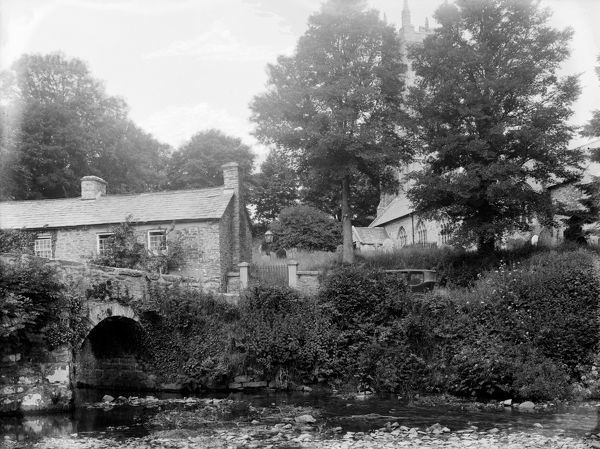 The photograph is taken from the ford over the river which probably predates the bridge. St Nun's Church can be seen behind the trees. A motor car, just in view, is parked near the churchyard gate. Photographer: Herbert Hughes