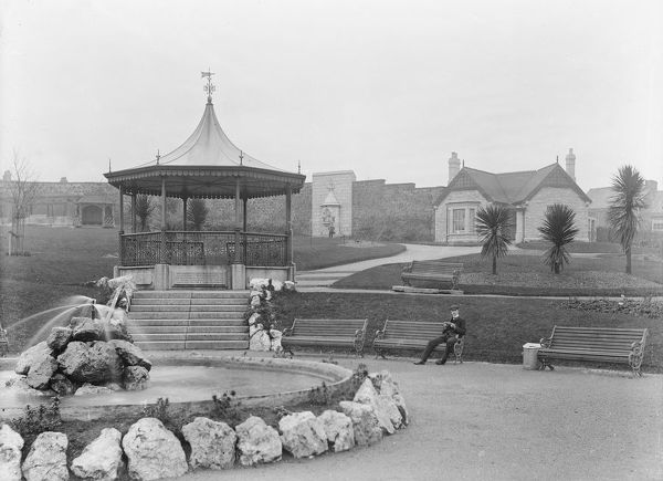 The bandstand at Victoria Gardens with a man sitting on a bench. The pond and fountain can be seen in the foreground and the gardener's home and drinking fountain in the background. Victoria Gardens was created to commemorate the Diamond Jubilee of Queen Victoria in 1897