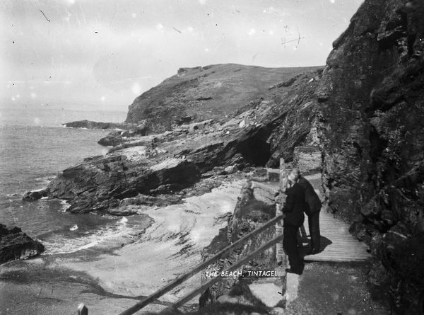 Barras Nose and the beach at Tintagel Haven, with two men standing in the foreground on the coastal path. Photographer: Unknown