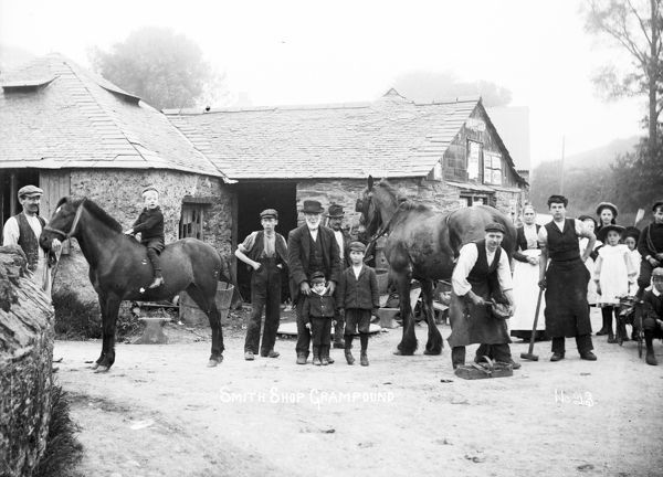 View of Blacksmith's shop on the west side of the River Fal. A horse is being shoed. A large group of people are watching. Photographer: Samuel John Govier