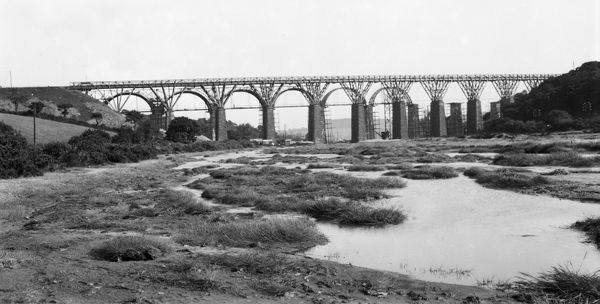 View of the Carnon Viaduct showing the original Brunel timber fan structure viaduct being replaced by a new stone structure directly behind the original. The new viaduct opened on 13th August 1933. Photographer: Herbert Hughes