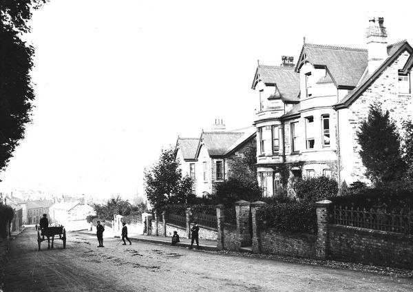 A general view down the hill to the incomplete cathedral, with a horse and cart and boys playing. Photographer: Arthur Philp