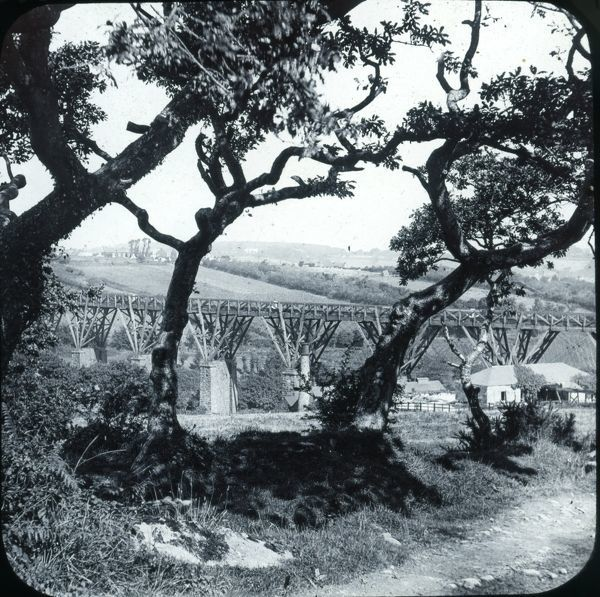 The original stone and timber Brunel viaduct seen through the trees. This was the last timber viaduct to be replaced in Cornwall, the new stone replacement opened on the 22 July 1934. Photographer: Unknown