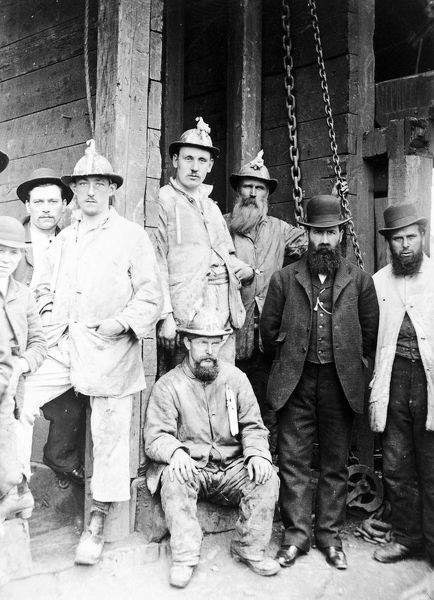 The photograph shows a group of men waiting to go underground. The man on the right with the white coat is probably the 'lander' or banksman. The man to his left, wearing the jacket and waistcoat, might be a mine Captain. Behind him is a man with a long beard