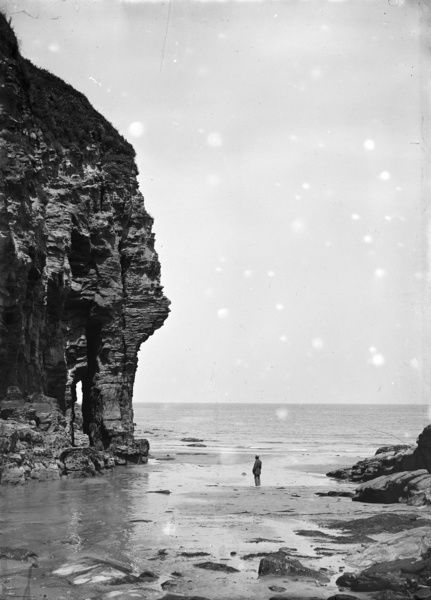 Man on the beach looking up at the rock. Photographer: Herbert Hughes