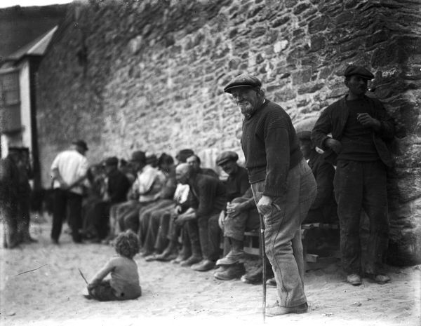 A group of fishermen seated against wall at back of the beach with a child in the foreground. Photographer: Unknown