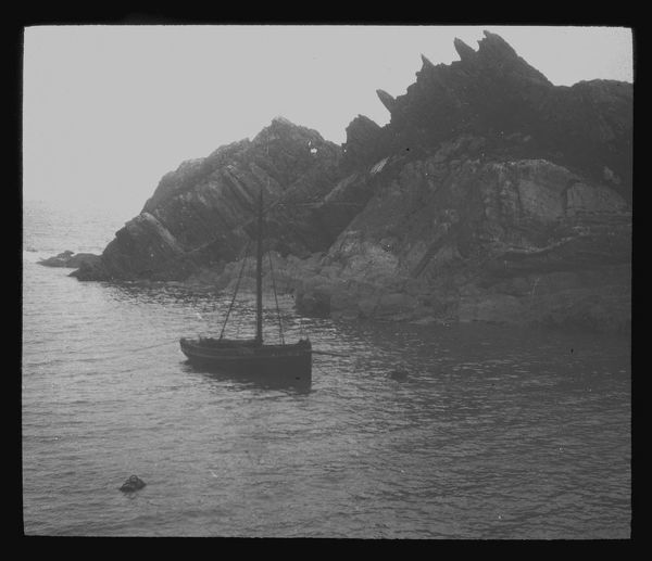 Fishing boat in a cove, probably Polperro, Cornwall. Around 1900