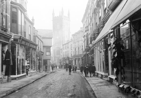 A view down Fore Street looking east, towards Holy Trinity Church, showing shops with outside displays and external lighting. A group of young schoolboys and a road sweeper are shown. Photographer: Unknown
