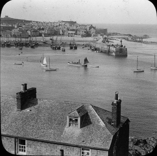 General view over the harbour towards the Island, before the building of Wharf Road. The remains of the wooden pier can be seen to the right of the picture. Number 38 in a series of glass lantern slides produced by William Charles Hughes, London
