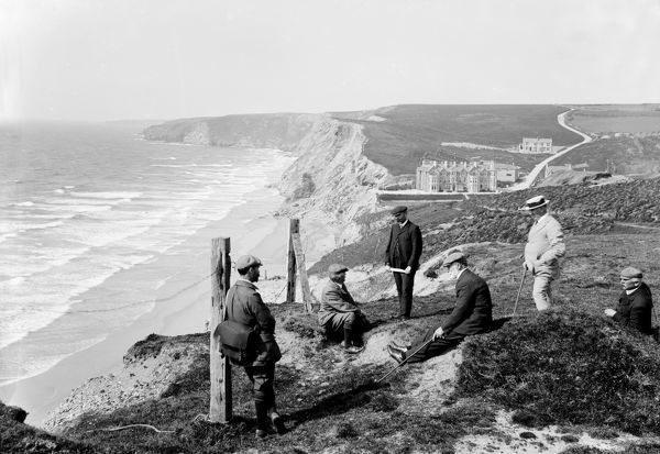 A group of men including Herbert Hughes and T. Mitchell, the photographers on the cliff top at Watergate Bay with the Watergate Bay Hotel in the background. Photographer: John Charles Burrow