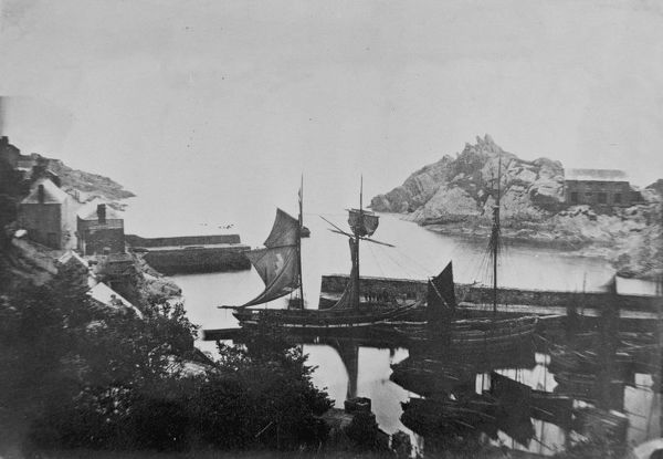 A schooner and other vessels in the harbour with Chapel Rock, also known as Peak Rock, behind