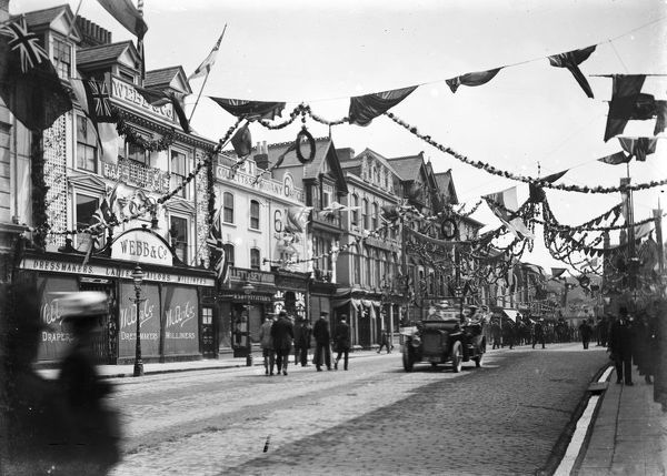 Boscawen Street looking east. The street is highly decorated, probably for the Bath and West Show. An open-top motor car is in the centre and the frontage of Webb & Co.'s drapers, Collett & Seymour and the Red Lion Hotel can be seen on the left