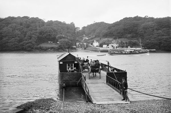 King Harry Ferry moored on the Philleigh side of the river. The steam driven chain ferry was introduced in 1888. Mr Wellington the ferryman, stands in the foreground with his ticket machine. The pleasure steamer S.S. Alexandra is sailing up river