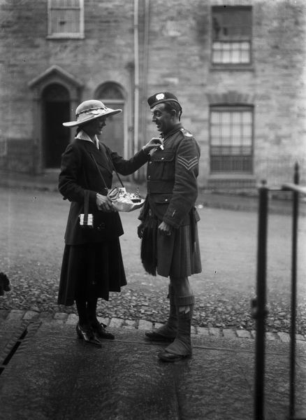 "Collecting day for ""Our Lady"" Day. The soldier is a sergeant in the 14th (County of London) Battalion, London Scottish Regiment. He has a ""Wound Stripe"" on the cuff of his uniform jacket. (see also TRUwef.6). Photographer"
