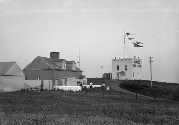 Lloyd's signal station with flags flying and a view of the adjoining buildings. Three ladies and a young child are standing outside the cottage in the foreground. Photographer: Arthur Philp