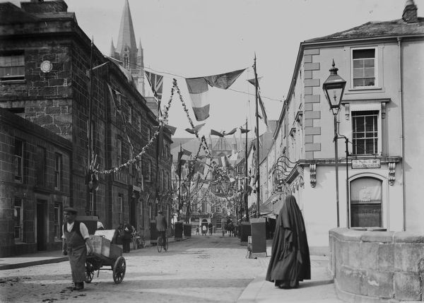 A view of Lower Lemon Street looking from Lemon Bridge towards Farrow's Bank and the Red Lion Hotel in Boscawen Street. The street is decorated with flags and garlands, possibly for the Coronation of George V in 1911, or maybe for the Bath