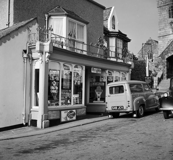 A shop in The Square with St Keverne Church on the right. A small van with registration plate 548 JCV is parked outside. Photographer: Charles Woolf