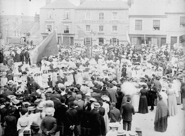 A crowd is gathered in Market Square (or Commercial Square) for a Tea Treat or similar occasion, maybe the Wesleyan Sunday School. The Wellington Hotel is in the background. Part of the A.K. Hamilton Jenkin collection. Photographer: Unknown