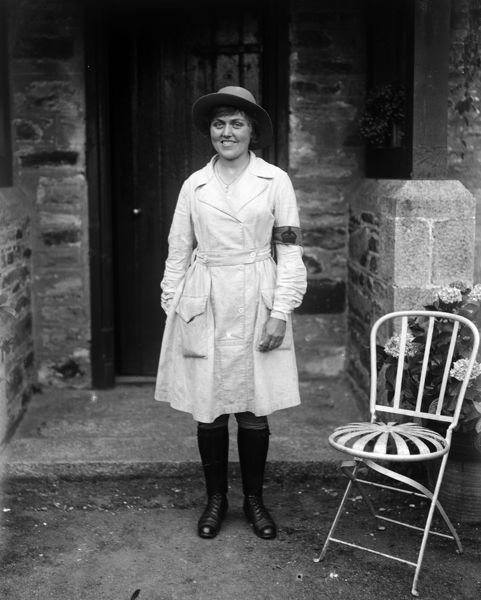 Ms. Nora Lock, a member of the Women's Land Army, standing outside the front door of Tregavethan Farm, a Women's Land Army training centre