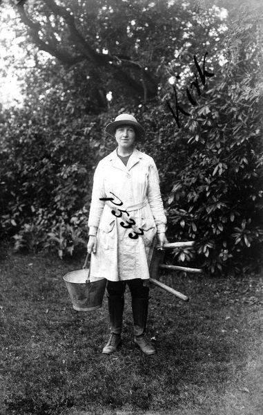 "A member of the Women's Land Army pictured with a milking pail and three legged milking stool. The name on the photograph is given as ""Kirk"". The woman's uniform consists of boots, gaiters, felt hat and pale fabric overalls. Photographer"