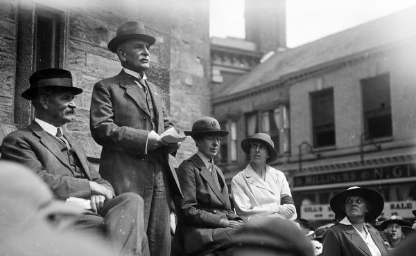 Man making a speech from a platform. Lady in WAAC uniform (with hat badge) seated to his left. Member of the Women's Land Army uniform seated to her left. Photographer: Arthur William Jordan