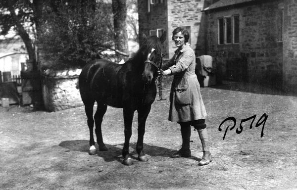 An unnamed member of the Women's Land Army standing in a yard, holding the bridle of an unsaddled horse. Photographer: Arthur William Jordan