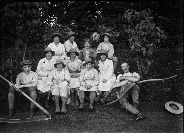 Eight members of the Women's Land Army at Tregavethan Farm, a Women's Land Army training centre. Also pictured are Mr & Mrs. Martin, Tregavethan's owners, their dog and a young man holding a scythe. Three of the women are named as follows