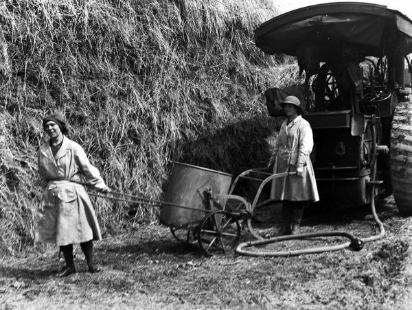 Two members of the Women's Land Army pulling a water cart in front of a Burrell Traction Engine with a water hose attached. Probably at Tregavethan Farm, a Women's Land Army training centre. Photographer: Arthur William Jordan