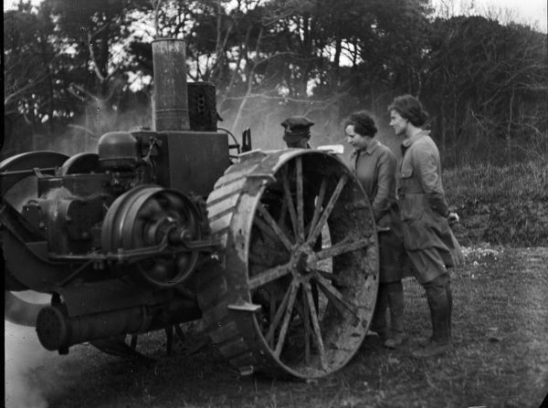 Two members of the Women's Land Army Girls being shown an early tractor by a man in army uniform. Photographer: Arthur William Jordan