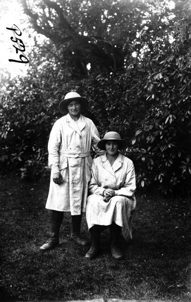 Two members of the Women's Land Army in a field at Tregavethan Farm, a Women's Land Army training centre. One of the women is standing and one is sitting. Their names are unknown. Photographer: Arthur William Jordan