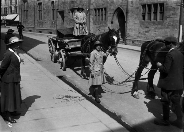 Two members of the Women's Land Army with a horse and cart in Princes Street, Truro. The woman on the cart is possibly Ms. Trejeweth and the woman leading the horse is possibly Ms. I. Crowther. Photographer: Arthur William Jordan